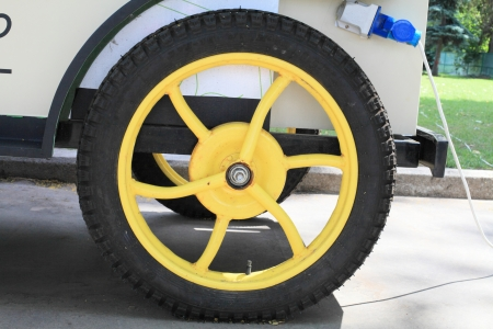 Car wheel bright yellow color close-up on the background of plants.