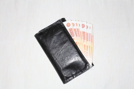 Black wallet and money of five-thousandth of Russia close-up on a light background.