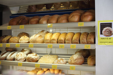 Showcase a variety of breads with price tags at the grocery store close-up in artificial light.