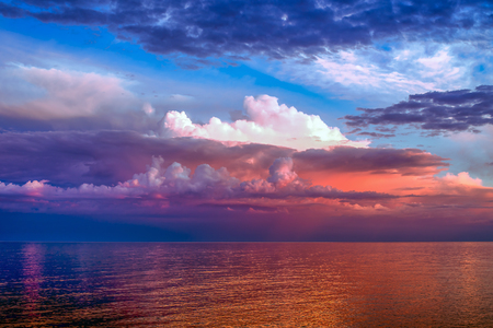 sunset clouds: Colorful clouds over large lake in the sunset light