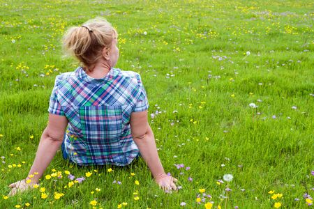 A woman is sitting on a green meadow