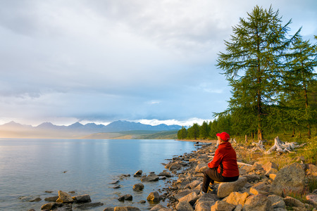 A woman looks at the lake Hovsgol in the sunset light. Peak Munku-Sardyk - near the center of the frame on the left. Eastern Sayan. Mongolia.