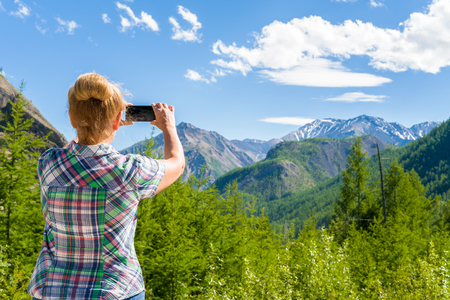 A woman is taking pictures of the landscape. Eastern Sayan, Siberia, Russia Stock Photo