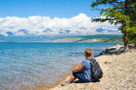 A middle-aged woman enjoys the view of Lake Hovsgol and the mountains of the Eastern Sayan. Mongolia