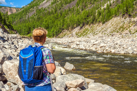 Woman backpacker looks at the mountain river