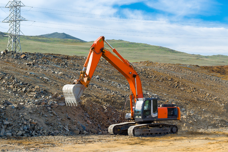 The excavator is building a new road near the power transmission line.