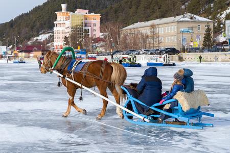 A horse harnessed to a sleigh rides tourists on the ice of Lake Baikal. Listvyanka, Siberia, Russia