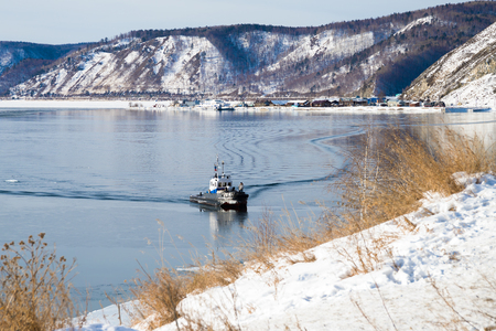 A small boat from the lake in winter. Baikal port is visible on the opposite bank.