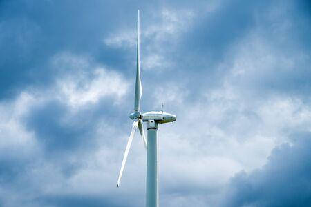Wind turbine on a cloudy sky background