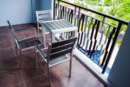 Hotel balcony with metal fence, table and chairs