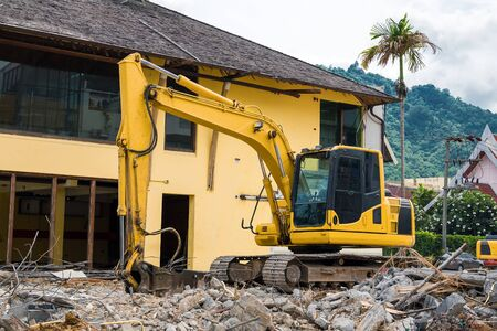 Excavator on the ruins of an old building