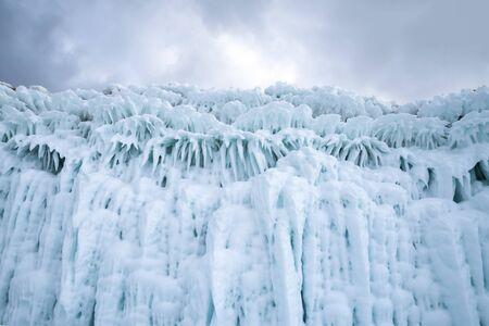 Beautiful turquoise icicles on the coastal cliffs of Lake Baikal. Siberia, Russia.