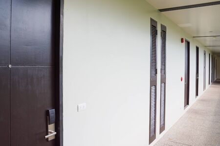The hotel's long corridor with doors and ventilation grilles. Фото со стока