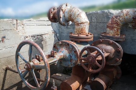 Abandoned concrete well with old rusty pipes and water-gate valves.