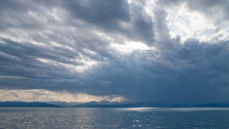 Evening cloudy sky over the sea and coastal mountains.
