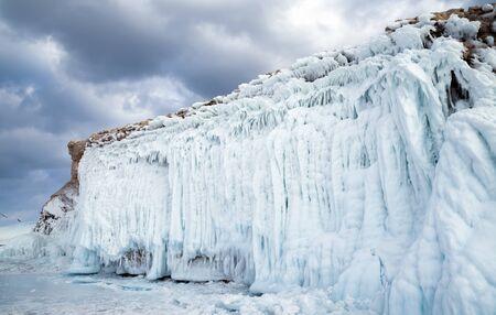 Sharga-Dogan island covered in icicles on lake Baikal in winter. Siberia, Russia.