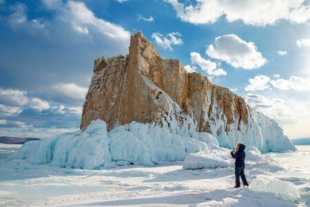 Woman tourist takes a photo on a smartphone of a beautiful island covered with icicles on Lake Baikal. Siberia, Russia.