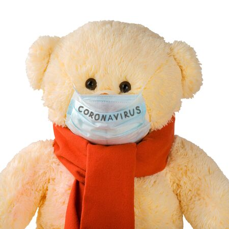Teddy bear with a scarf and a mask with the inscription coronavirus isolated on white.