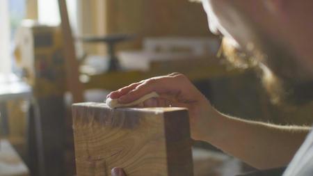 口ひげとあごひげを生やした木工業集中の肖像画は、ワーク ショップで木の板にラッカーをこすり