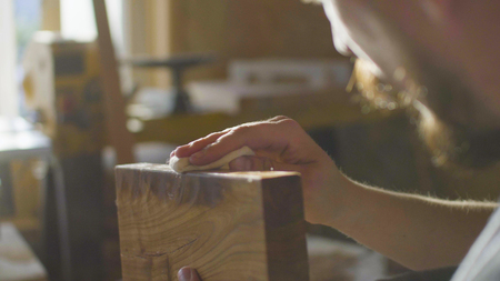 Portrait of concentrated bearded woodworker with moustache rubs lacquer in a wooden plank in workshop