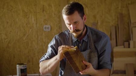 Close-up van handen van timmerman schrijnwerker in schort schort lakens op een houten plank op de tafel