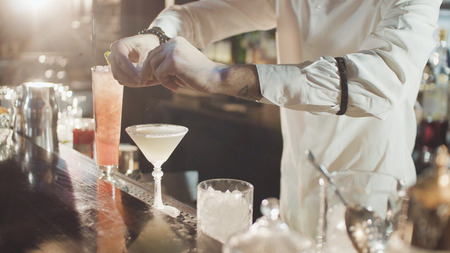 20s professional bartender in white shirt and black hat is preparing mixing cocktail in night club bar Stock Photo