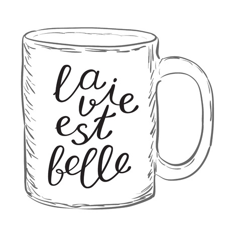 est: La vie est belle. Life is good in French. Brush hand lettering. Handwritten words on a sample mug. Great for mugs, posters, throw pillow cases, t-shirts design, home decor and more.