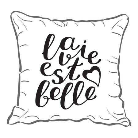 est: La vie est bell, life is beautiful in French. Brush hand lettering on a sample throw pillow. Great for pillow cases, posters, photo overlays, home decor and more.