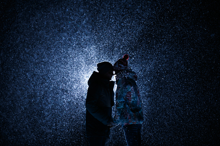 silhouette Man and girl at night under the snow. met today embrace and kiss. Suitable for sport theme, snowboards or skis. A lot of snow Banco de Imagens