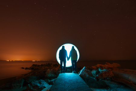 young romantic couple in love standing on the shore of the great river in the winter night. Making of Freezelight