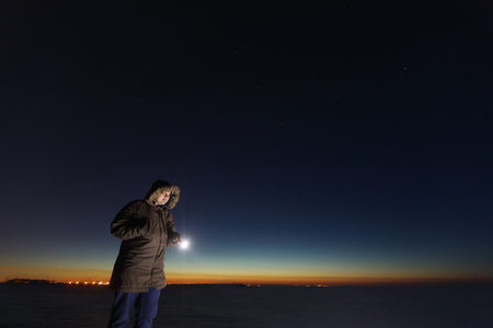 Silhouette of a man with a flashlight, observing beautiful, wide blue night sky with stars and visible Milky way galaxy. Astronomy, orientation, clear sky concept and background Banco de Imagens