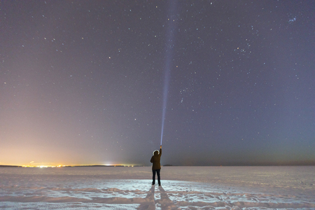 Silhouette of a man with a flashlight, observing beautiful. Astronomy, orientation, clear sky concept and background. UFO and searching, waiting miracle, torch