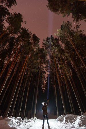 Man with flashlight in forest. Search or expect extraterrestrial life or aliens. Searching for yourself, signals the universe. Alone in the woods, surviving Banco de Imagens