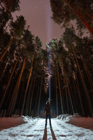Man with flashlight in forest. Search or expect extraterrestrial life or aliens. Searching for yourself, signals the universe. Alone in the woods, surviving Stock Photo