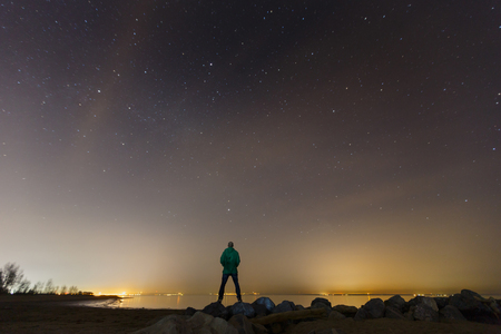 The Man and the Universe. A person is standing on the top of the hill next to the Milky Way galaxy with a tripod in his hands