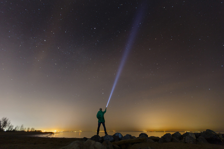 Silhouette of a man with a flashlight, observing beautiful, wide blue night sky with stars and visible Milky way galaxy. Astronomy, orientation, clear sky concept and background. Stock Photo