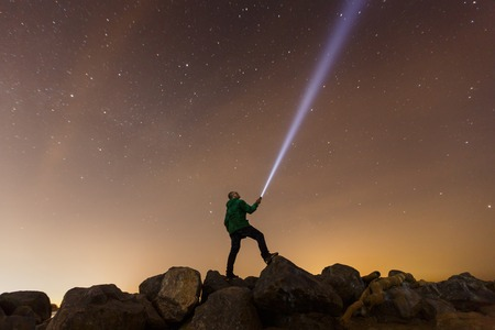 disoriented: Silhouette of a man with a flashlight, observing beautiful, wide blue night sky with stars and visible Milky way galaxy. Astronomy, orientation, clear sky concept and background. Stock Photo