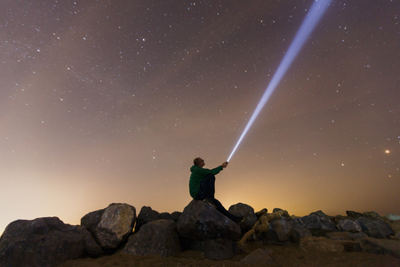 Silhouette of a man with a flashlight, observing beautiful, wide blue night sky with stars and visible Milky way galaxy. Astronomy, orientation, clear sky concept and background. Banco de Imagens