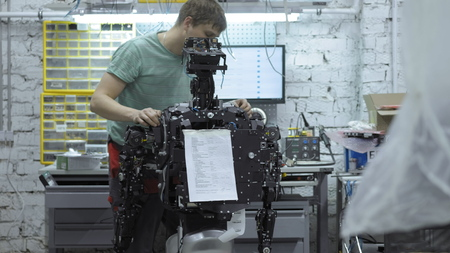 the engineer makes and adjusts the modern robot. The robot at the factory for the production of robots. Workplace of innovative engineer.