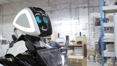 A new white robot stands in a loft room. Plant for the production of robots. The robot blinks and smiles.