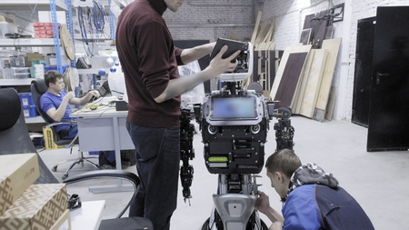 Factory for the production of robots. Two engineers are examining a robot. Creates a new robot in the lab. Connect the face of the robot, the robot smiles.