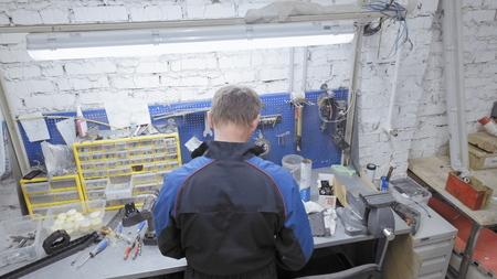 Repairman worth his work table. Workspace auto repair wizard. Imagens