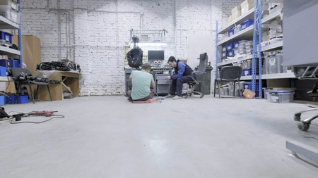 Factory for the production of robots, modern robotic developments. Two employee engineers create a technical robot.