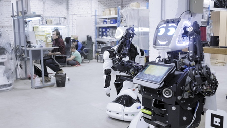 Factory for the production of robots. The robot is worth disassembled, smiling.