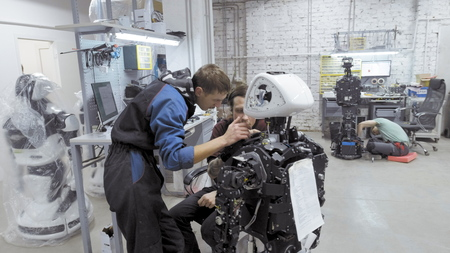 Factory for the production of robots. Two engineers are examining a robot. Creates a new robot in the lab. Repairs individual parts of the robot. Check the performance