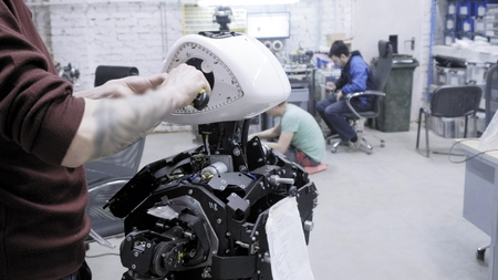 Factory for the production of robots. Two engineers inspect robots. Creates new robots in the lab. Customize disassembled robot Banco de Imagens