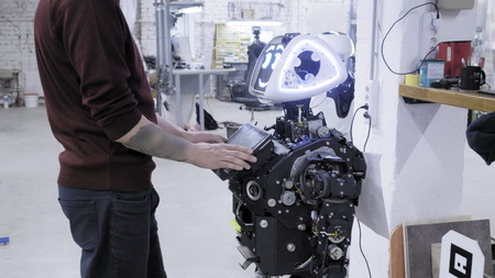 Factory for the production of robots. The engineer examines the robot. Creates new robots in the lab. Configures disassembled robot Banco de Imagens