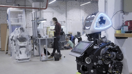 Factory for the production of robots, modern robotic developments. The disassembled robot waves his hands in greeting and dances in the workshop. Engineers walk in the background.