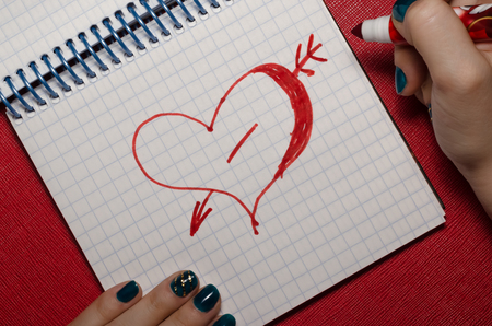 The girl drawing heart pierced by an arrow a marker in  noteboo