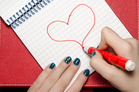 The girl heart drawing a marker in  notebook for Valentine Day.